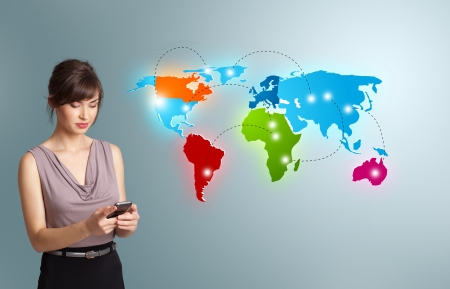 communications: Beautiful young woman holding a phone and presenting colorful world map Stock Photo