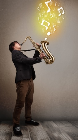 Handsome young musician playing on saxophone with musical notes photo