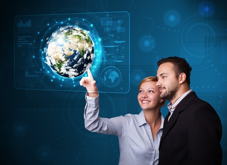 Happy young couple touching high-tech 3d earth panel photo