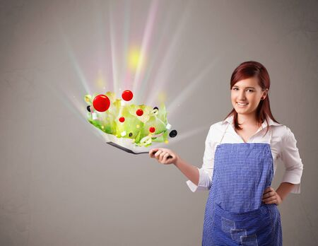 Beautiful young woman cooking fresh vegetables with abstract lights photo