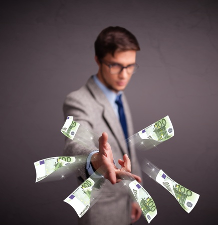 Handsome young man standing and throwing money photo