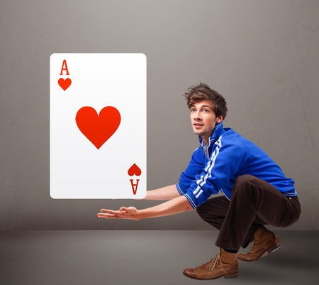 Attractive young man holding a red heart ace photo