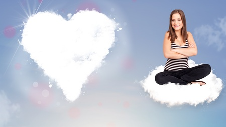 Beautiful young lovely woman sitting on cloud with heart photo