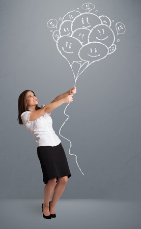 Happy young woman holding smiling balloons drawing Stock Photo - 21298063