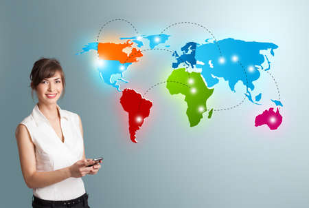 intercontinental: Beautiful young woman holding a phone and presenting colorful world map Stock Photo
