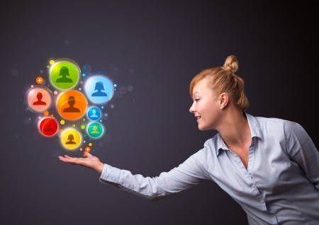 medias: Young businesswoman holding colorful social network icons in her hand Stock Photo