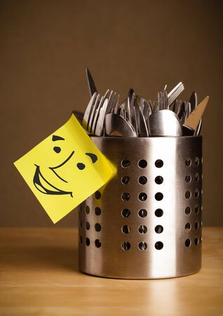 Drawn smiley face on a post-it note sticked on a cutlery case photo