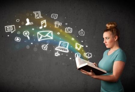 interaccion social: Se�ora joven que lee un libro con los iconos de multimedia que sale del libro Foto de archivo