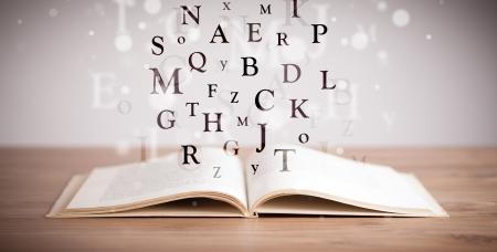 Geopend boek met vliegende letters op concrete achtergrond