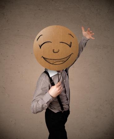 Zakenman die een kartonnen smiley emoticon in de voorkant van zijn hoofd