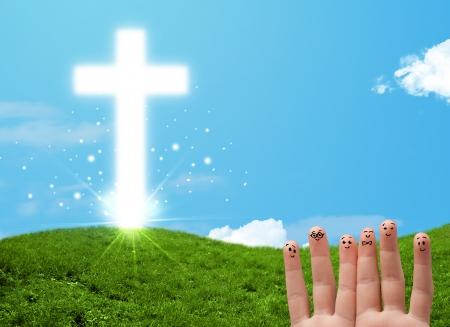 familia cristiana: Feliz dedo caras sonrientes en la mano con una cruz cristiana religi�n Foto de archivo