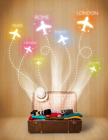 du lịch: Túi du lịch với quần áo đầy màu sắc và máy bay bay trên nền grungy