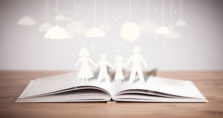 stories: Cardboard figures of the family on opened book. The symbol of unity and happiness