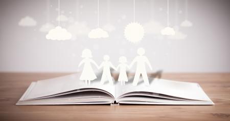 Figuras de cartón de la familia en el libro abierto. El símbolo de la unidad y la felicidad Foto de archivo