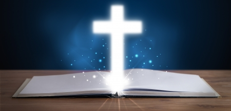 christian symbol: Open holy bible with glowing cross in the middle on wooden deck Stock Photo