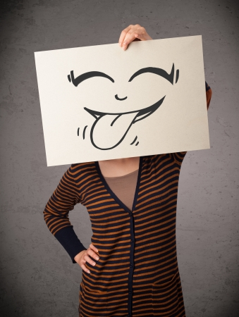 Young woman holding a paper with a cute smiley face on it in front of her head photo
