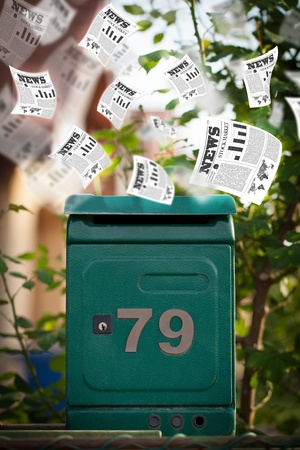 Post box with daily newspapers flying out photo