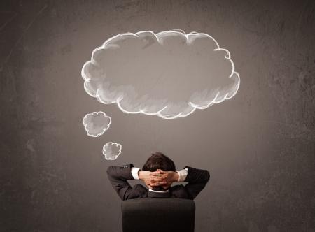 Jonge zakenman zitten in bureaustoel in voor een muur met cloud gedachte geschetst op een bord boven zijn hoofd