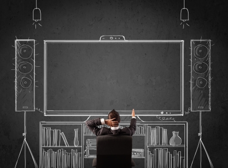 Young businessman sitting and enjoying home cinema system sketched on a chalkboard Stock Photo - 21536528