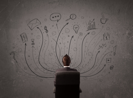 Young businessman sitting and deciding in front of a chalkboard with sketched arrows and signs in different directions Stock Photo - 21536536