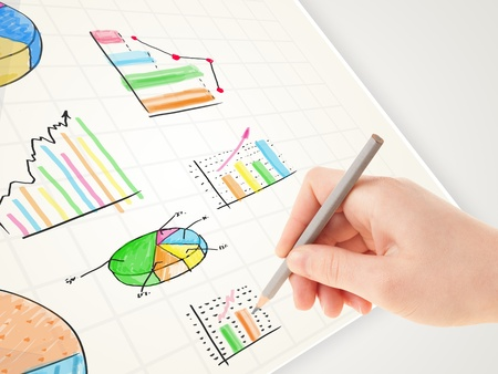 Business person drawing colorful graphs and icons on plain paper Stock Photo - 21578517