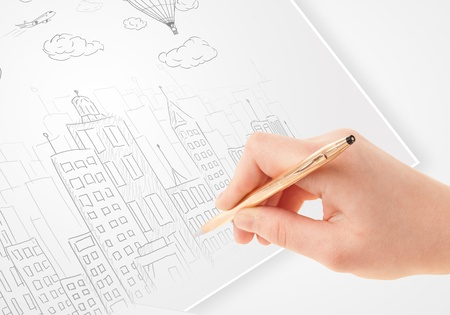 A person drawing sketch of a city with balloons and clouds on a plain paper Stock Photo - 21578500