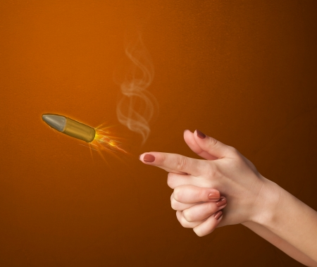 Gun shaped woman hand with bullet coming out of it photo