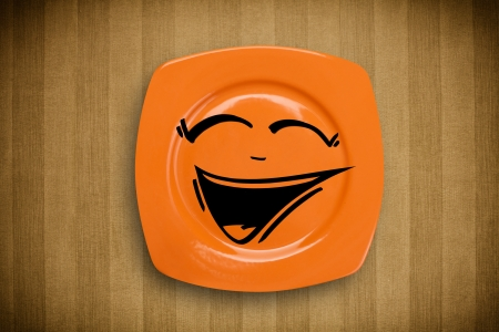 Happy smiley cartoon face on colorful dish plate and grungy background photo