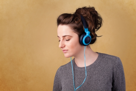 Pretty young woman with headphones listening to music with empty space Stock Photo - 21739637
