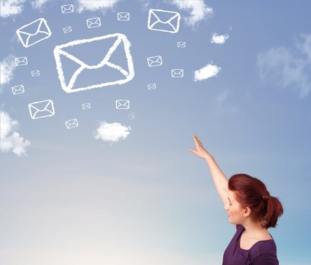 Casual young girl looking at mail symbol clouds on blue sky photo