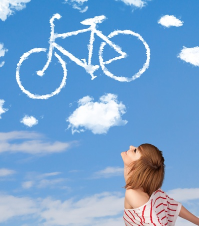 Young casual girl looking at bicycle clouds on blue sky photo