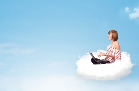 Pretty young woman with laptop sitting on cloud with empty space photo