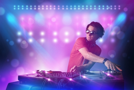 disc jockey: Young disc jockey mixing music on turntables on stage with lights and stroboscopes Stock Photo