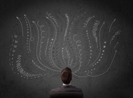 Thoughtful young businessman sitting and deciding in front of a chalkboard with sketched arrows and lines in different directions photo