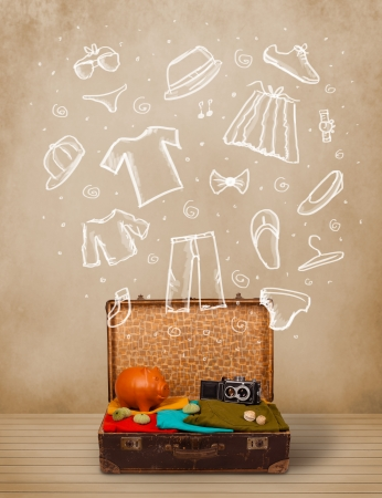 Traveler luggage with hand drawn clothes and icons on grungy background photo