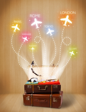 Travel bag with clothes and colorful planes flying out on grungy background photo