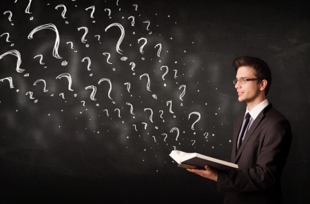 Confused man reading a book with question marks coming out from it photo