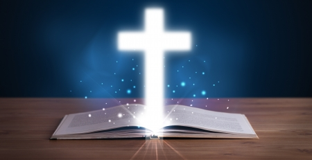 Open holy bible with glowing cross in the middle on wooden deck photo
