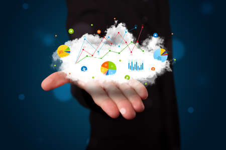 Young businessman presenting cloud with charts and graph icons and symbols photo