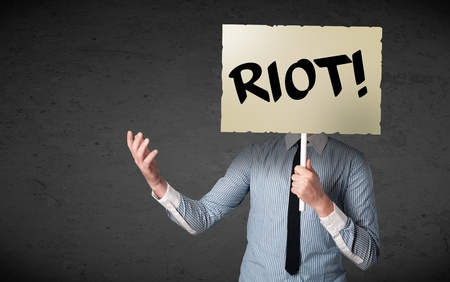 Businessman holding a demonstration board with riot sign in front of his head photo
