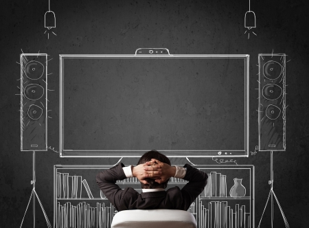 Young businessman sitting and enjoying home cinema system sketched on a chalkboard Stock Photo - 21740231