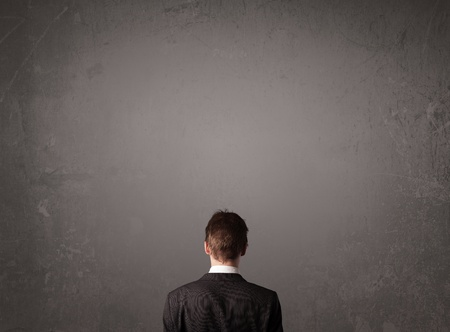 Young businessman standing in front of a wall with copy space photo