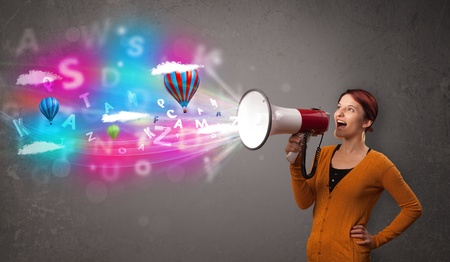 Cute girl shouting into megaphone and abstract text and balloons come out photo