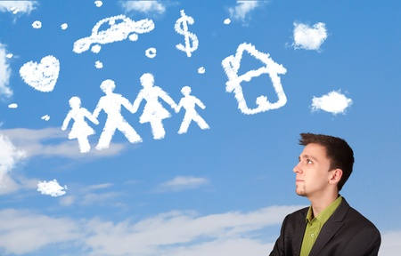 Businessman daydreaming with family and household clouds on blue sky photo