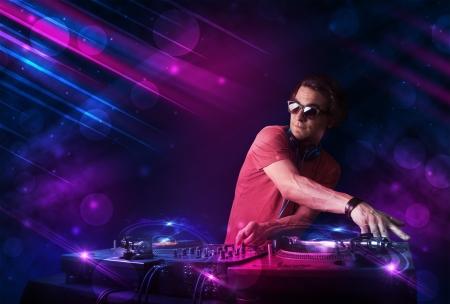 auriculares dj: DJ joven atractiva jugando en platos con efectos de luz de color