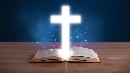 historias de la biblia: Abrir Santa Biblia con la cruz que brilla intensamente en el centro de la cubierta de madera