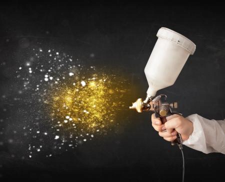 pulverizador: Trabajador con la pintura del aerógrafo con pintura dorada y resplandeciente partículas