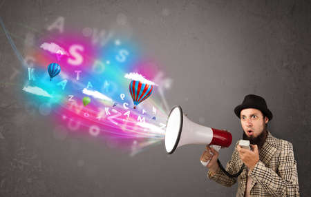 Handsome man shouting into megaphone and abstract text and balloons come out photo