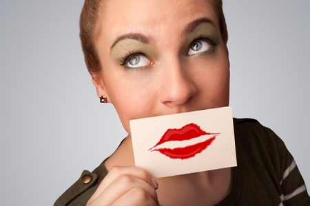 Happy pretty woman holding card with kiss lipstick mark on gradient background photo