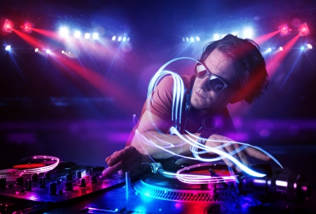Handsome disc jockey playing music with light beam effects on stage photo